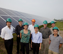 group of people next to solar panels