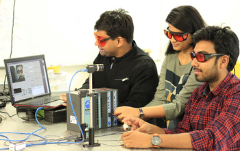 Three students with laptop and optical equipment.