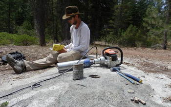 researcher with a gas-powered, water-cooled drill for sampling bedrock