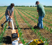 Two scientists install a weather station in an agricultural field.