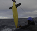 Scientist with a seaglider as it's lowered into the ocean