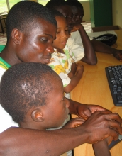 Older student helps younger student at the Ghana fab lab.