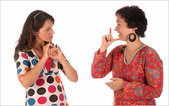 Two women communicate using sign language.