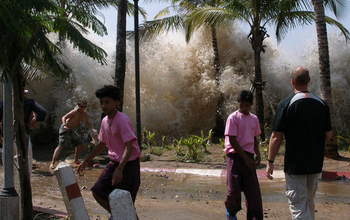 People running away from a tsunami-caused wave