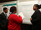 Students explaining a poster.