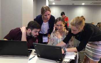 Awardee Cayelan Carey (far right) shows students how to run lake models on computers at a workshop.