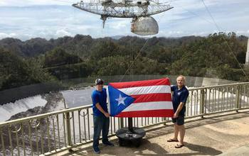 Arecibo staff hold up a Puerto Rico flag with the telescope array in the background.
