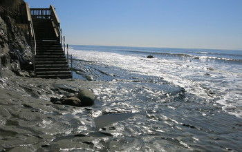 Exposed bedrock platform at beach access staircase, where large waves swept away the sand.