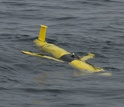 A coastal glider floats along the ocean surface, soon to sample water.