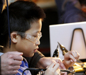 A father and son work on soldering to make an automaton out of copper wire.