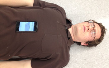 A smart phone placed on a man's chest to monitor breathing