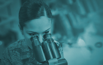 A woman in Air Force uniform looks through a microscope.
