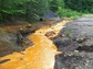 Acid mine drainage flowing through a stream in western Pennsylvania forest.