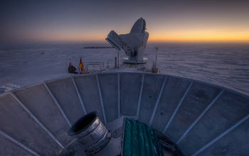 sun setting behind BICEP2 and the South Pole Telescope at Amundsen-Scott South Pole Station.