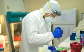 A researcher in protective gear works in a lab.