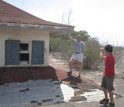 E. Bruce Pitman and colleague next to a house damaged by mudslides in Montserrat