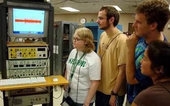 students gathered next to a rack of scientific equipment
