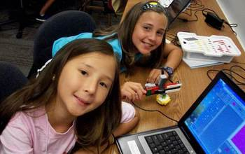 Girls from the Georgia Computes summer camp  next to a laptop