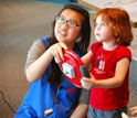 A volunteer at the Science Museum of Minnesota helps a young girl play a driving simulation.