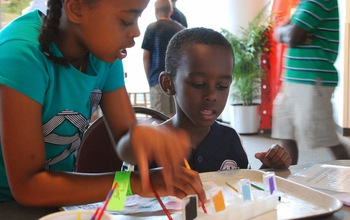 Young museum visitors use a paint set of acids and bases to learn about pH.
