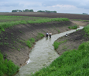 Scientists measure water velocity and collect samples in an agricultural ditch.