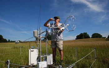 A scientist works on a carbon dioxide flux tower in a field