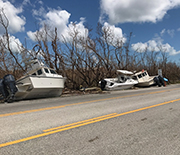 A highway with several boats beside it, blown onto land by Hurricane Irma.