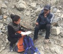 A woman research assistant interviews a quake survivor in Mustang District.