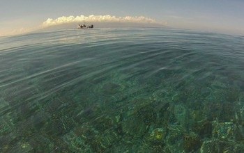 An NSF Moorea Coral Reef LTER site research boat is moored on an outer reef; background is Tahiti.