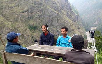 Photo showing two researchers interviewing locals in the mountains