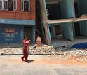 woman walking on a street with damaged buildings after the quake.