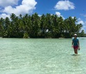 Graduate student Ana Miller-ter Kuile walks in the shallows in front of an islet at Palmyra Atoll