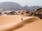 Man walking up sand dune in the Sahara Desert.