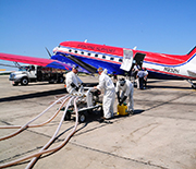 Workers loading chemical dispersants onto an airplane.