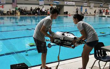 Students by the pool with device at 12th Annual ROV Competition