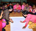 women drawing a map at a community gathering