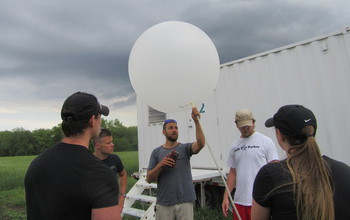 A research team of four men and one woman prepare to launch a weather balloon.
