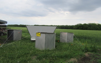 Instruments to measure air temperature and winds in an agricultural field.