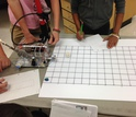 Middle school students in a lab conduct accuracy tests with a pheumatic catapult.