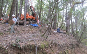Researchers drilling a borehole in forest