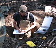 Patch of ground in the Pacific Northwest, with scientist making soil analyses.