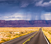 View of clouds, mountains, flatlands, and two-lane road during an intense rainstorm in Arizona.
