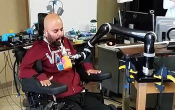 Man in a chair drinking from a cup held by a robotic arm