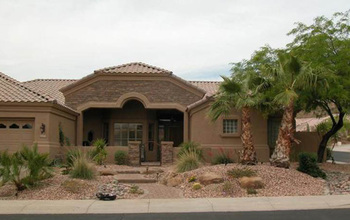 Photo of a house  with  xeriscaping featuriing a stone garden and palm trees