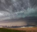 Photo of sky and a large wall cloud arcs around a rotating thunderstorm updraft in Nebraska.