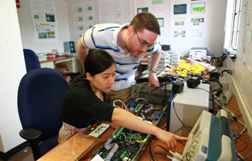 Image of two students with electronic devices for the electric power transmission system.