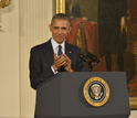 Photograph of President Obama applauding at a podium