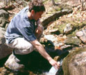 Photo of a scientist collecting a stream sample at the Hubbard Brook LTER Site.