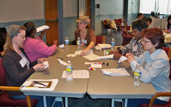 Photo of women entrepreneurs seated around a table doing team-building exercises.