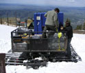 Photo of aerosol-tracking instruments being loaded onto a snow cat at the Storm Peak Lab.